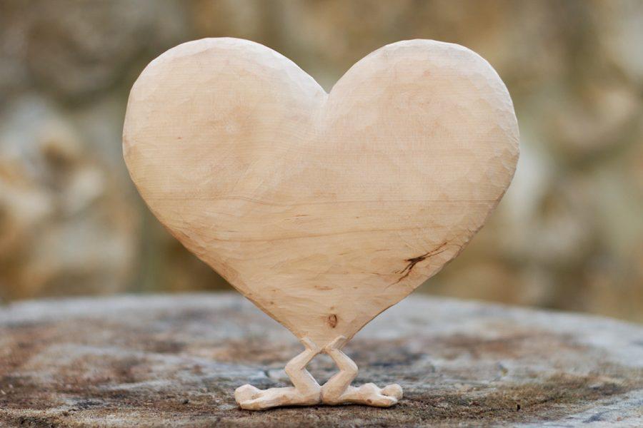 Skulptur zwei Personen mit Herz aus Holz geschnitzt.